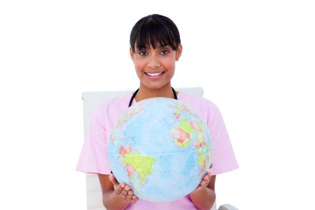 nurse who chose a travel nursing career holding a globe