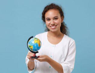 smiling travel nurse holding globe