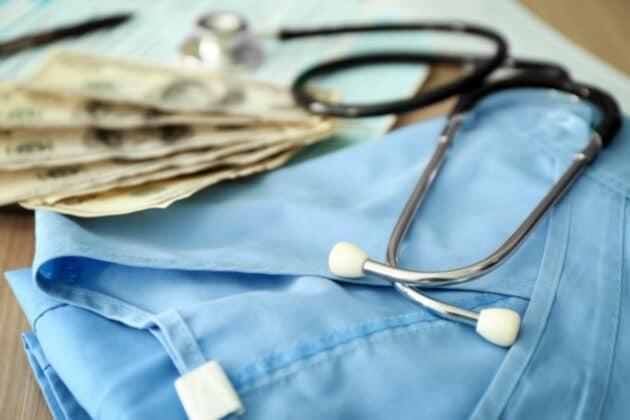 travel nurses uniform next to stethoscope and next to money